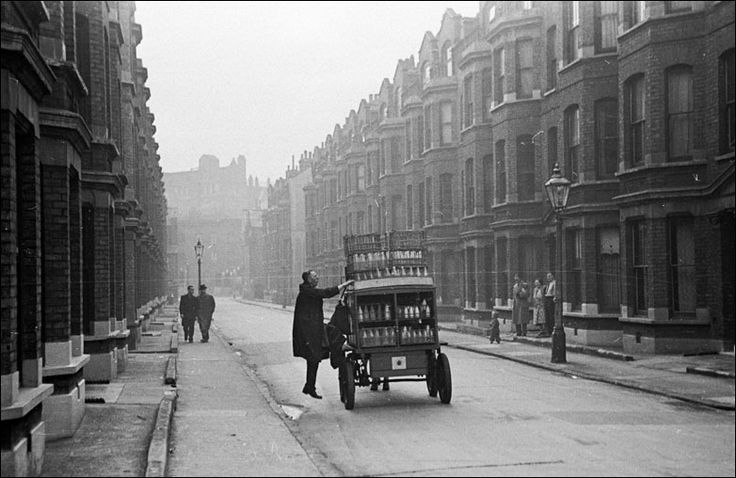 A man climbs onto a Southwark milk cart near the Elephant and Castle in South London, England. Original Publication: Picture Post - 4694 - Life At The Elephant - pub. 5 January 1949.
