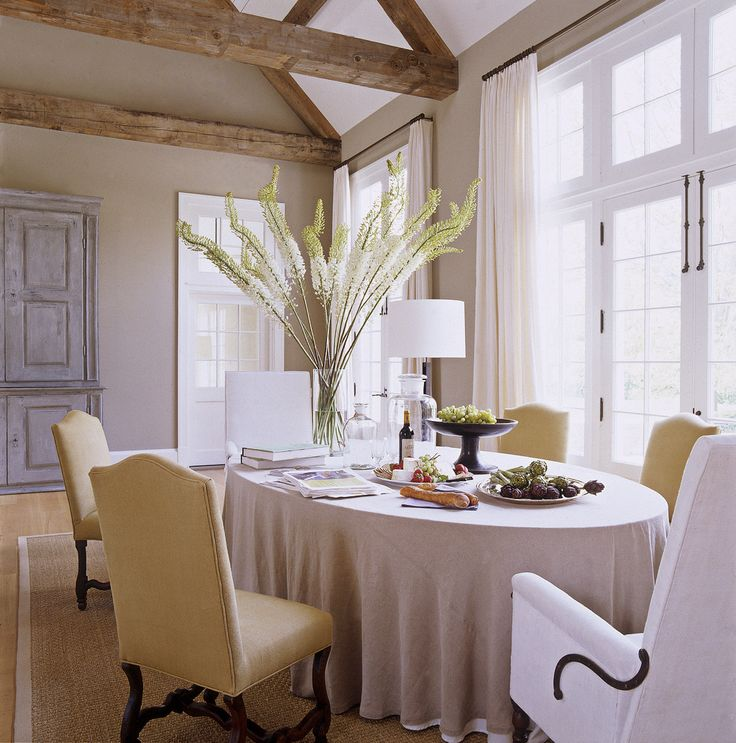 Here Ina has the dining table all set and ready for guests. Stately upholstered chairs mean everyone is comfy at dinnertime.   - HouseBeautiful.com