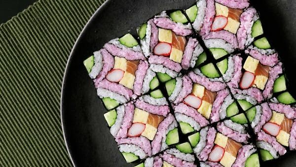 Recipe with video instructions: This beautiful square mosaic sushi deserves to be framed in a food art museum. Ingredients: 150g rice with 1 tbsp sushi vinegar (for white sushi rice), 200g rice with 1 tbsp sushi vinegar (for pink sushi rice), 1 cucumber, 2 tbsp denbu (sweet fish flakes), 3 sticks imitation crab, 20g salmon, 8 sticks tamagoyaki (Japanese omelette), 4 sheets nori