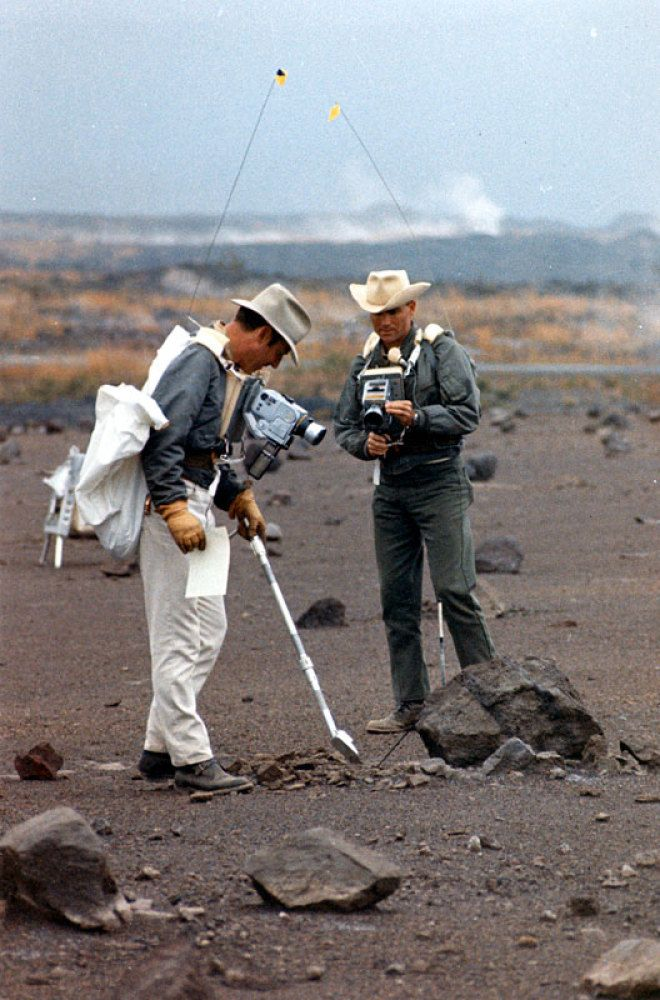 Jim Lovell (left) points with his scoop while Fred Haise takes a documentation photograph during the December 17-20 field trip to Hawaii. December 1969. Scan by Ed Hengeveld. NASA