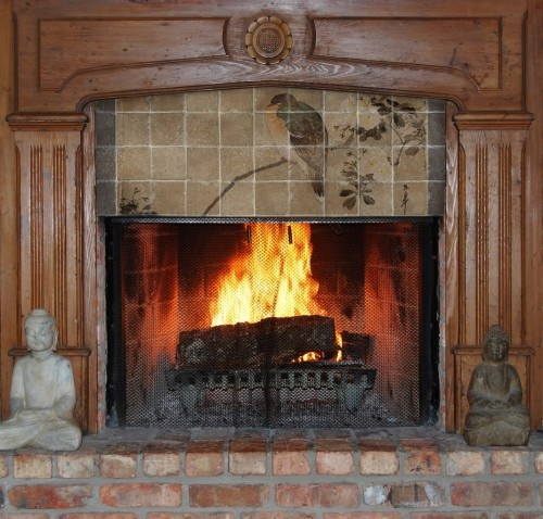 Asian tile mural on marble tiles above fireplace in family room. Decorative marble tiles blend with a rustic fireplace to create a unique fireplace remodeling idea.