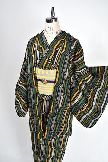 グレーとブラックのダークカラーにグリーンとクロムイエローがアクセントになったカラーリングも素敵に、トリックアートのような幾何学ストライプが織りだされたウールのアンサンブル(着物と羽織のセット)です。