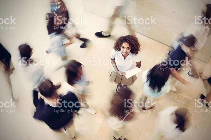Nervous student standing still in busy private school hallway royalty-free stock photo