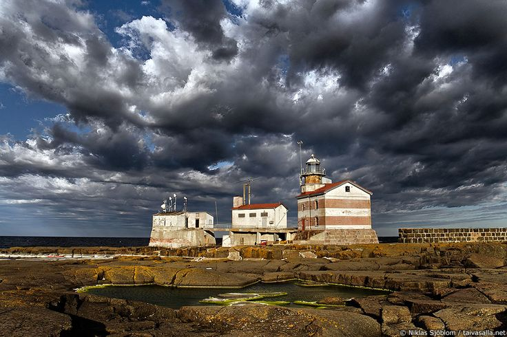 Märket lighthouse on a stormy morning. The border between Finland and Sweden runs through the small Märket island in the Baltic Sea. The pool in the front is in Sweden, while the lighthouse and the two other buildings are located in Finland.