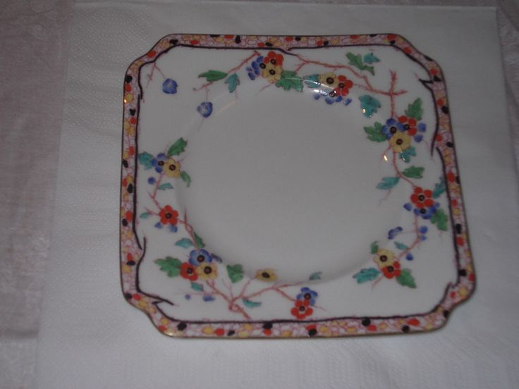 Doulton deco: Spring square side plate, H3904, c1931 (4). Red, yellow and blue flowers and green foliage on white ground, with abstract multicoloured border and black edging and gold gilt trim.
