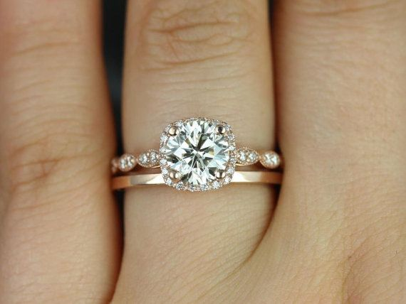This engagement ring is designed for those who love simple with a slight twist. The round cut in the center is traditional while the cushion halo