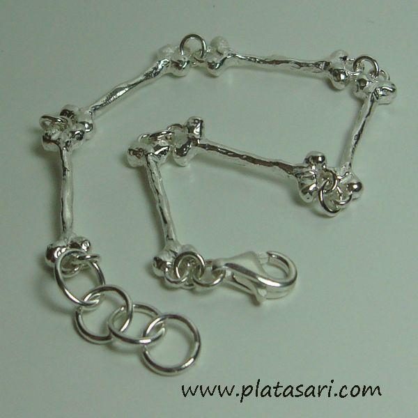 Pulsera de plata con diseño de huesos.