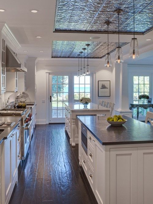 PIN 1: This award winning Nantucket style kitchen features a hand-stamped tin ceiling over the dual islands. The combination of the crisp white walls, the dark walnut floors, the Cohiba antiqued granite and Calcutta Gold marble countertops with the embossed tin ceiling create a stunning space.