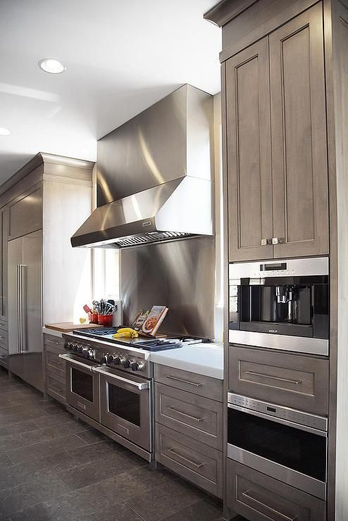 Amazing kitchen features a stainless steel kitchen hood which stands over a stainless steel cooktop backsplash, flanked by windows, over a Wolf Duel Fuel Range with a stainless steel French door refrigerator to the left and a built-in coffee machine and microwave to the right.