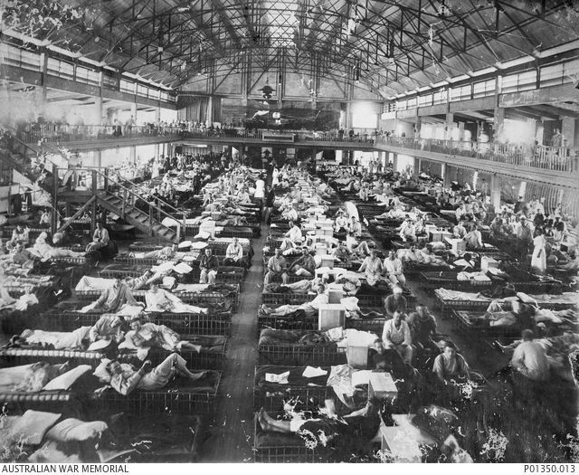 HELIOPOLIS, EGYPT, 1915. THE INTERIOR OF NO. 1 AUSTRALIAN AUXILIARY HOSPITAL, FORMERLY THE LUNA PARK SKATING RINK. CASUALTIES FROM GALLIPOLI OCCUPY BEDS OF PALM-WOOD, KNOWN AS ANGERIBS.