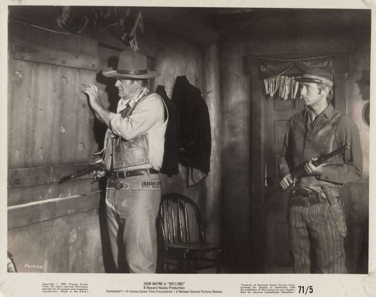 RIO LOBO - John Wayne & Chris Mitchum prepare to shoot it out with the bad guys - Directed by Howard Hawks - Publicity Still.