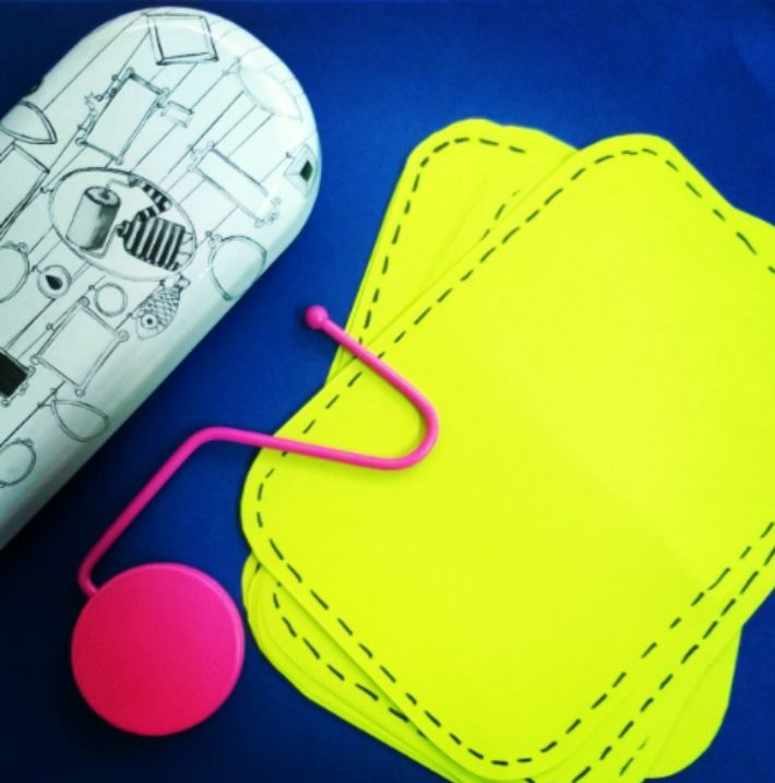 Lime green patches, pink bag hanger and black and white glasses case on a blue poster paper.