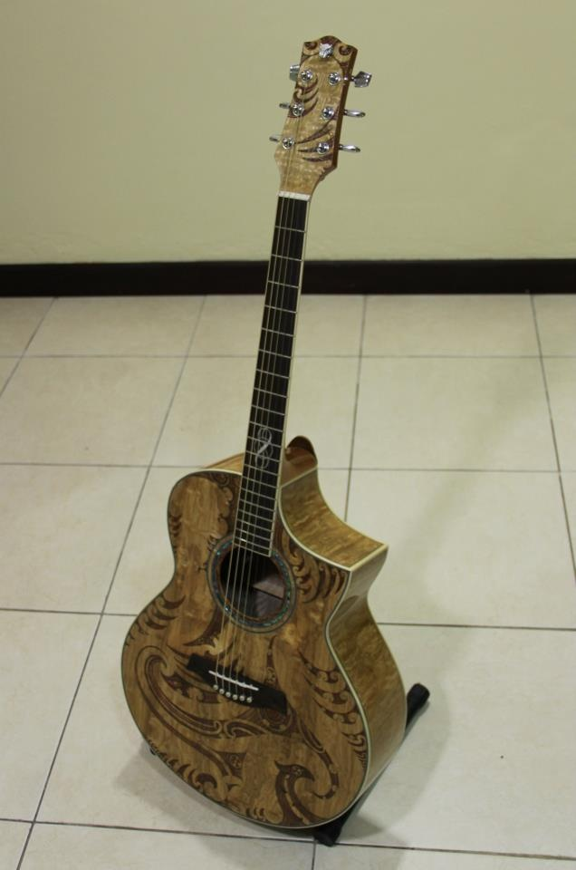 guitar with maori designs carved into it.