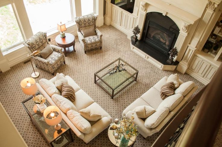 Warm and cool tones are balanced through the use of patterns in this space. A subtly patterned rug grounds the living room, while cream sofas create an inviting seating area.