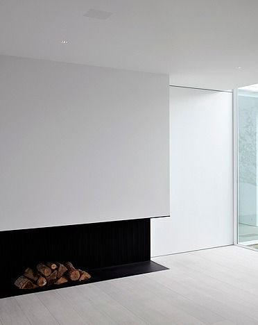 Bold black steel fireplace constrasting with a  white interior by Pascal Bilquin and Minus architects.