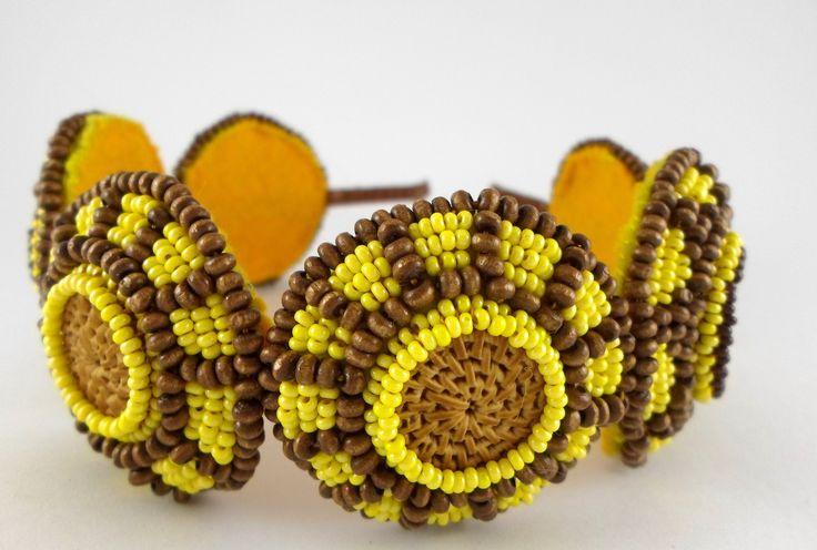 Přírodní ... čelenka Čelenka je tvořena dvěmi většími a čtyřmi menšími kotouči. Barevná kombinace žluté a hnědé je navržena tak, aby se barvy vzájemně hezky podtrhovaly. Čelenka je zpracována metodou korálkové výšivky a peyotovým stehem. Je potažena hnědou saténovou stuhou. Kovový základ čelenky umožní lepší variabilitu.