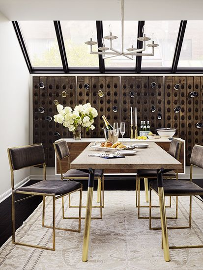 Love the use of multiple champagne stands on the wall of this wine room.  The brass table and chair legs add polish without overwhelming.