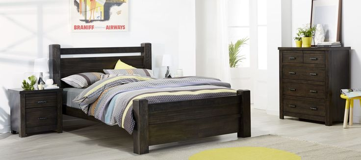 Sakeh dark wood grain bedroom furniture suite with grey, yellow and pastel patterned linen and décor