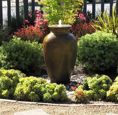Fountain nestled in landscaping.