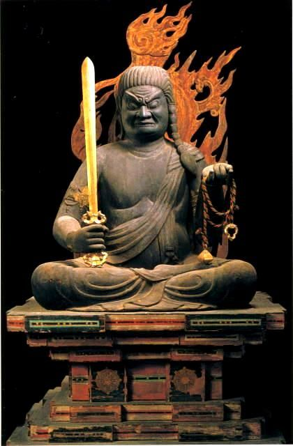 "Fudo-Myoo. He carries ""kurikara"" or devil-subduing sword in right hand (representing wisdom cutting through ignorance); holds rope in left hand (to catch and bind up demons); and is seated on rock (because Fudo is ""immovable"" in his faith)."