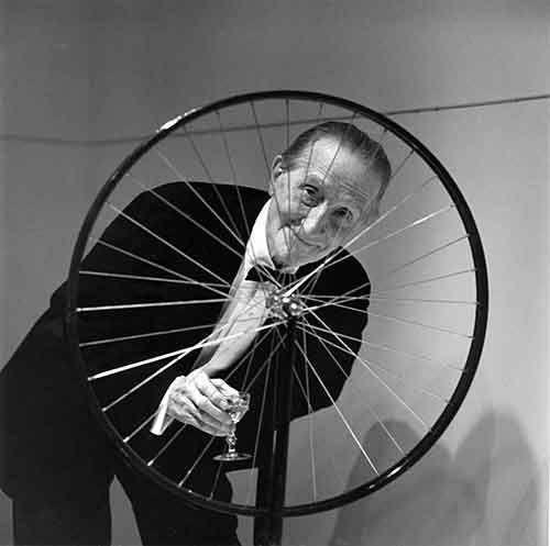 Marcel Duchamp sorridente dietro allla sua opera Ruota di bicicletta
