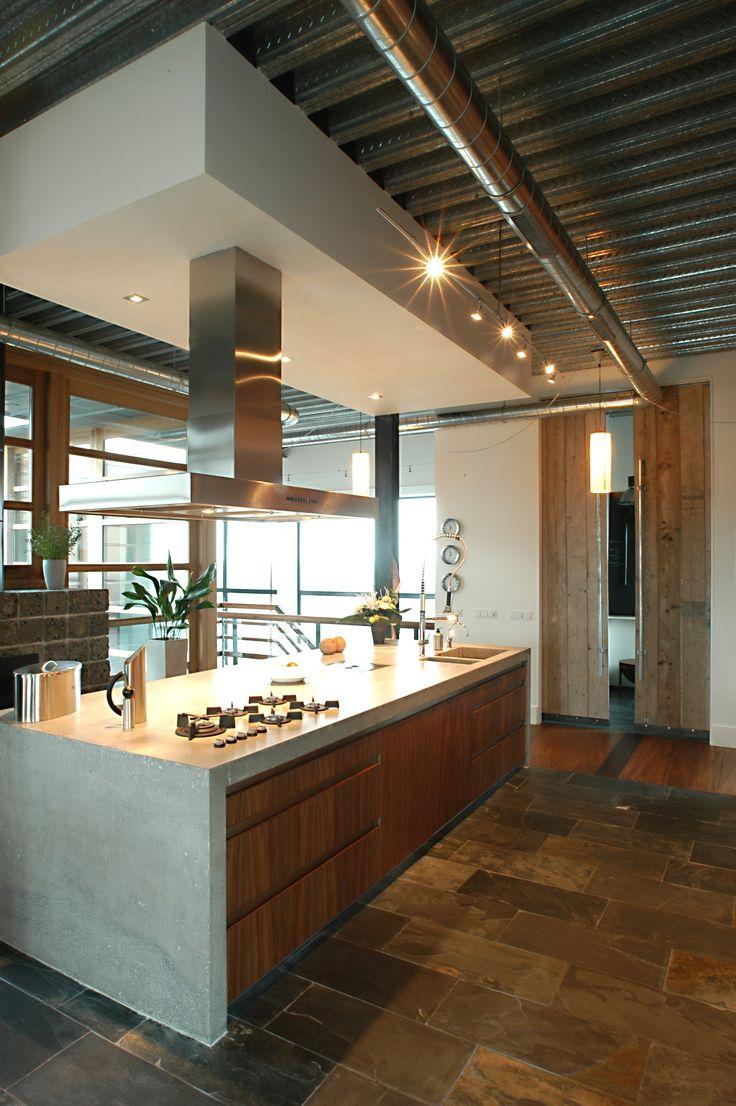 Maatwerk keuken met ter plaatse gegoten werkbladen, inclusief betonnen zijwanden. Greeplijst RVS. Noten houten fronten