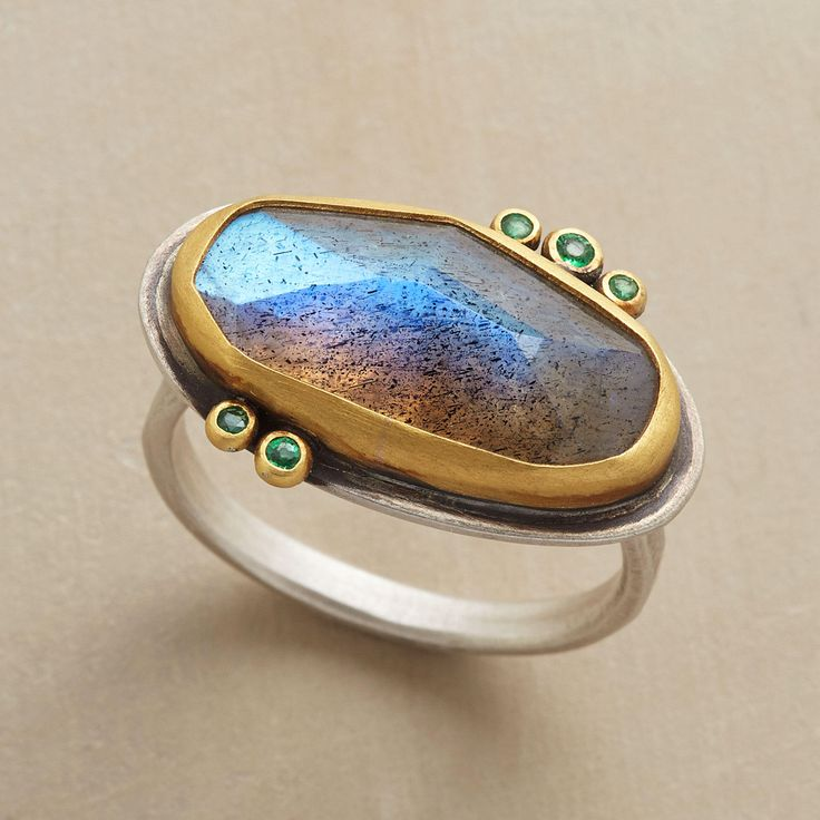 EMERALD DOTTED RING -- Gleaming emeralds dot the irregular perimeter of faceted labradorite, the stones set in 22kt gold on a sterling silver band. Handmade in USA by Ananda Khalsa. Whole sizes 5 to 9.