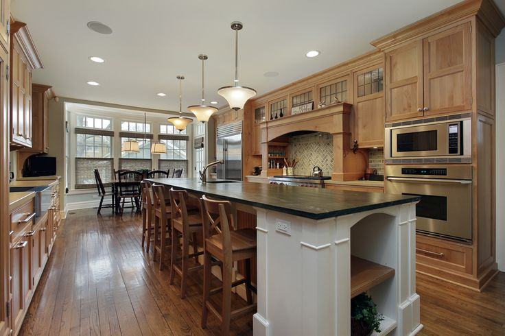 Custom wood kitchen with wood floor. Cabinets span both sides of the room with a long dark-topped island down the center. Dining area at end of the kitchen