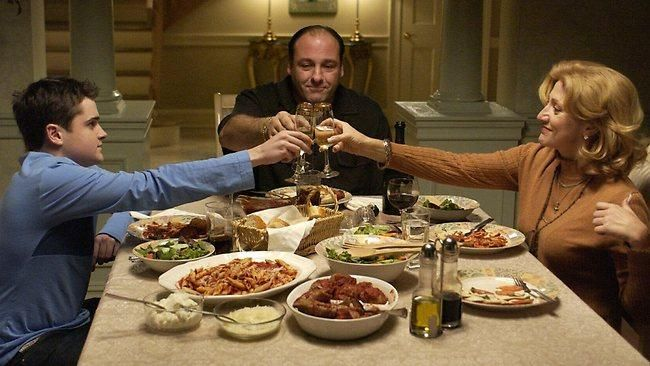 Actors Robert Iler (C), with Edie Falco (L) and James Gandolfini toasting with drinks at the dinner table in The Sopranos
