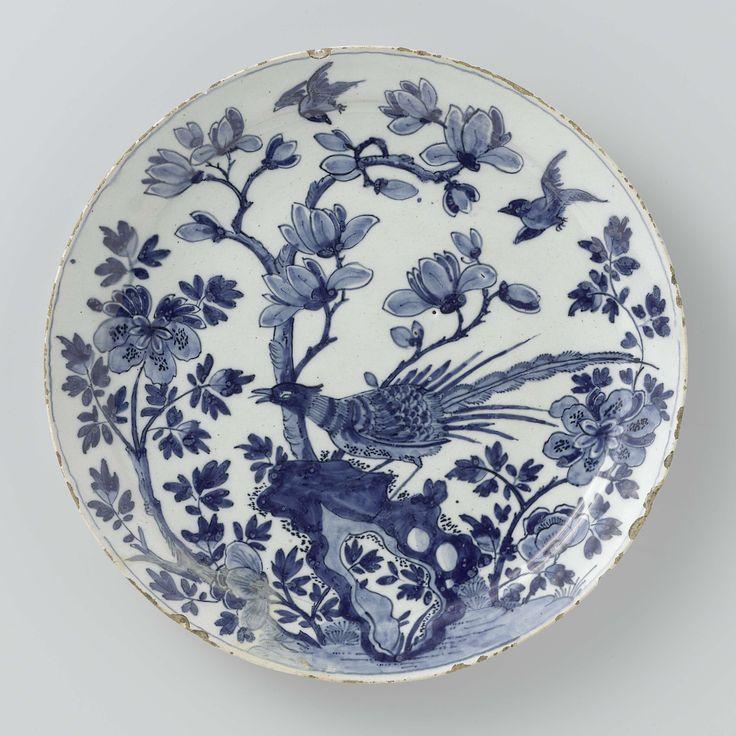 De Metaale Pot | bord van faience, De Metaale Pot, Lambertus van Eenhoorn | bord van aardewerk, blauw beschilderd op een wit fond. Voorstelling van een vogel staande op een rots. Erachter bomen en struiken, in de lucht nog twee vogels. Chinees geïnspireerd.