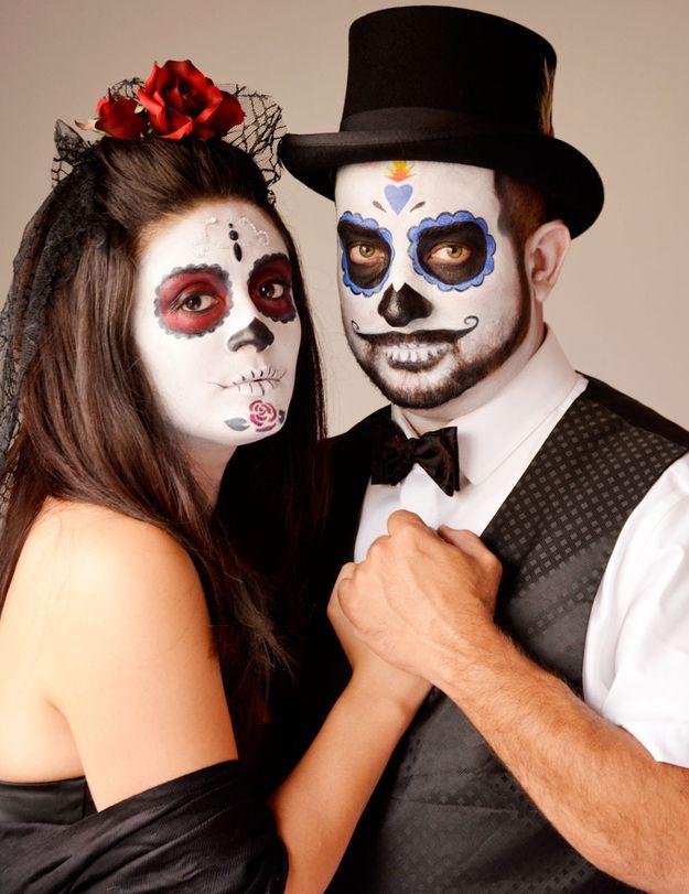 People dress up as a catrina and catrin.   29 Breathtaking Día De Los Muertos Photos