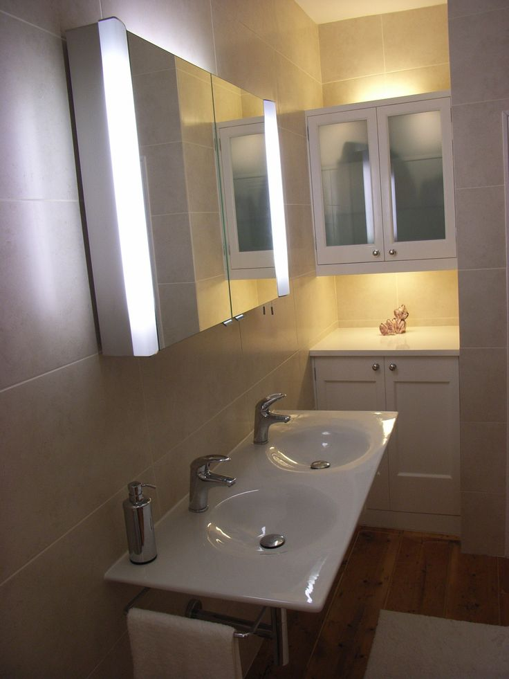 Double handbasin in bathroom with mirror cabinet and additional bespoke storage.