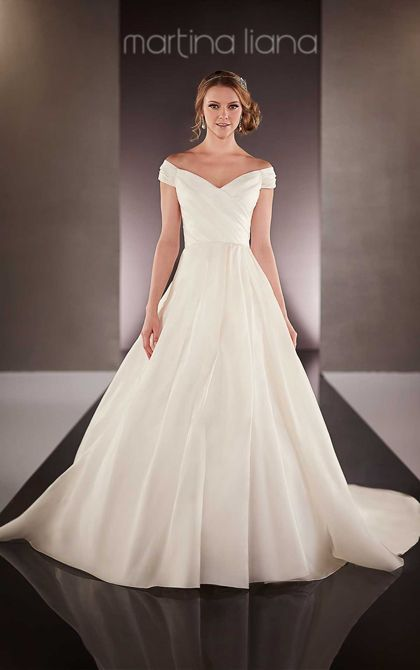 This elegant Silk Satin Organza A-line bridal gown from the Martina Liana wedding dress collection features a ruched bodice with thick off-the-shoulder straps. The back zips up under fabric-covered buttons that carry through to its elegant train.
