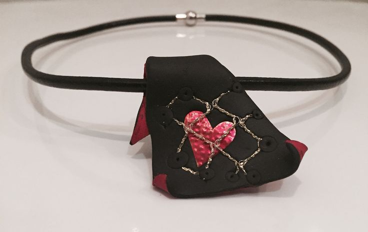 Handmade necklace. Black and red polymer clay with copper heart enamelled in red imprisoned in a metal net.