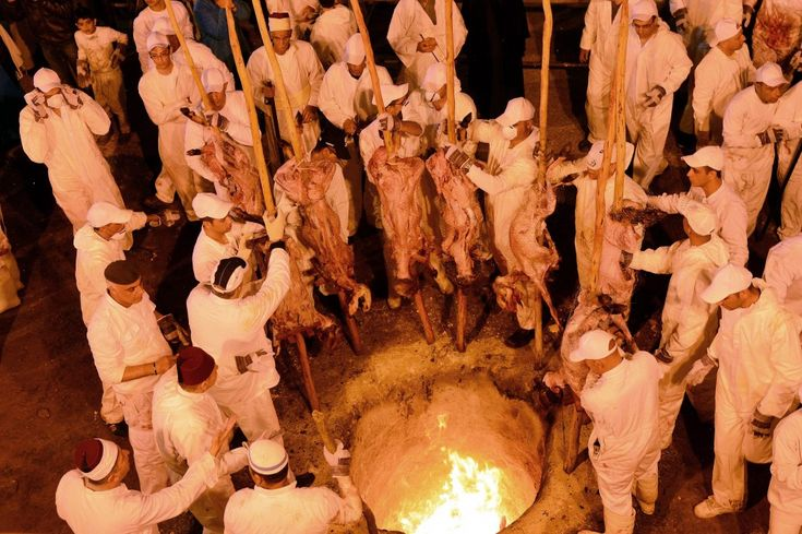 Samaritan worshipers insert their skewered Passover sacrifices into the oven during the ritual sacrifice, part of a Samaritan Passover ceremony on Mount Gerizim near the West Bank town of Nablus, April 23, 2013 (photo credit: Yossi Zeliger/Flash90)