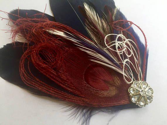 Nuestra inspiración vintage fascinator de SIDNEY es elegante. Hecho de una base de plumas azules marino, tiene una pluma de pavo real de Borgoña/berry con detalles de plumas azul marino, marfil y Burdeos. Decorada con volutas de rizado de mano Burdeos y marfil del pavo real y un hermoso cristal imitación con adorno de plata. Se fija con una pinza. ¡Total GLAMOUR! Cada pieza está hecha a la orden para el tamaño puede variar, pero esto es aproximadamente de 4.5 por 4.5.
