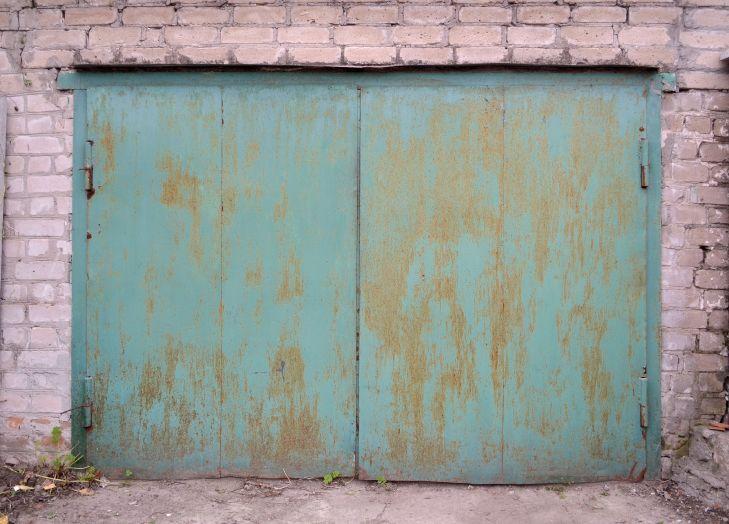 Garage green iron gates with rust. Гаражные железные ворота зеленого цвета с ржавчиной