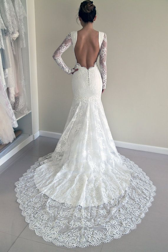 Lace wedding dress in a fit and flared trumpet silhouette with see-through lace panels in sides and an open back  The wedding gown has a stunning