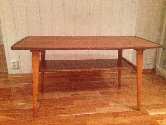 Teak bord med magasin hylle. Teak hylle er integrert i bjørk understell.' Mål: l:106 cm, b: 56 cm,, h: 55 cm. Minstepris kr 1200,- eller gi bud.