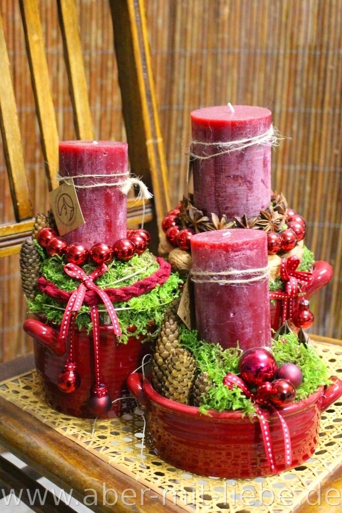 Adventsgestecke in dunkelrot; Kerzengestecke zum Advent in glänzender roter Keramik mit Zapfen, Kugeln, Bändern, Anissternen und Moos