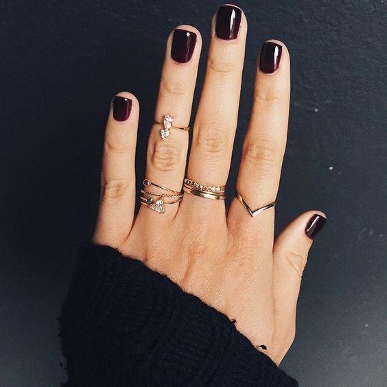 dark manicure., short nails, multiple rings