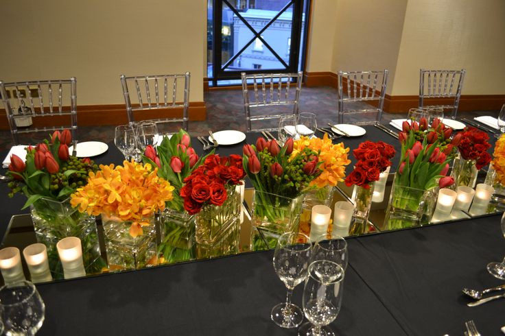 Long table centrepiece in red and yellow florals. Styled by Greenstone Events.