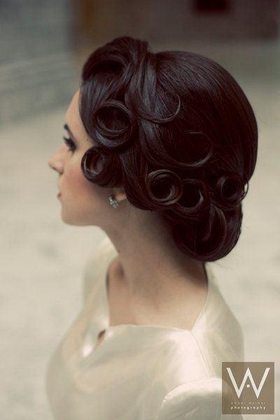 A chic and classic chignon low in the back, dressed up with fingerwaves and pin curls on the sides captures the beauty of the 1940s style.