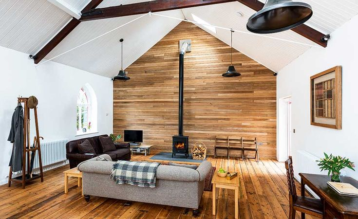 A cosy fireplace stands in front of a double-height timber clad wall in a chapel conversion