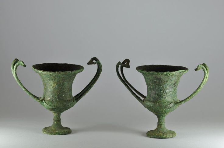 Greek bronze vessels, Greek  bronze kantharos, a pair, 4th century B.C. Greek bronze vessels, Greek kantahros with flaring mouth on raised foot, the two upturned handles with finely cast leaf attachment plates, 11.3 cm high and 11.7 cm high. These cups are example of the luxury tableware produced by Greek bronzesmiths in the late fourth century B.C. in order to satisfy the ambitions of the Macedonian kings to develop a sophisticated court art. Private collection