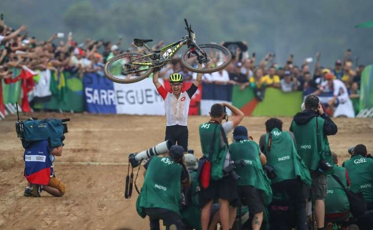 Nino Schurter of Switzerland celebrates after winning gold in the men's cross country mountain bike competition during the Rio 2016 Summer Olympic Games at Mountain Bike Centre.  Guy Rhodes, USA TODAY Sports