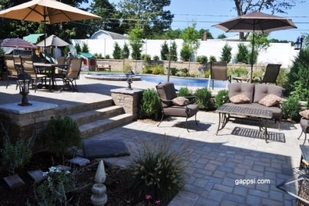 This backyard has a patio with two separate levels. The top level is the main level of the backyard, with the pool, grass area, and dining set. The pool in this yard is free formed with an attached hot tub. Behind the pool is a retaining wall topped with Evergreen trees providing privacy from neighbors. Two steps down and you are in a relaxing seating area. Both patios are made of Cambridge paving stones. Multi-leveled patios add beauty and flow to any backyard…