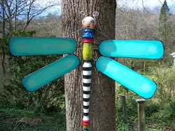 yard art - This looks to me to be ceiling fan blades and a table leg.  Paint any color - fun!