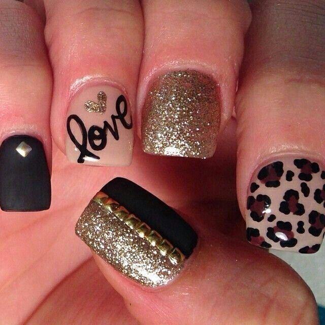 Animada manicura de uñas en negro, dorado y beige, decoradas con tachuelas doradas, estampado de leopardo, un corazón dorado y la palabra love.