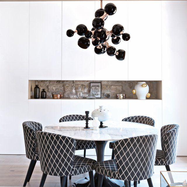 """Une salle à manger de marbre blanc et d'or noir. Dans le coin salon, les placards ont été intégrés au maximum pour ne pas encombrer l'espace. Table de salle à manger avec plateau en marbre Netto et chaises """"Aston"""" surplombés par une magnifique suspension noire et cuivrée."""